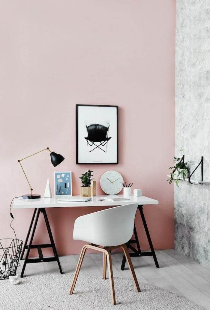 two tone living room walls, room with one pink and one grey wall, white desk with black legs, white chair with brown legs, black and white image in black frame, pale grey floor and rug