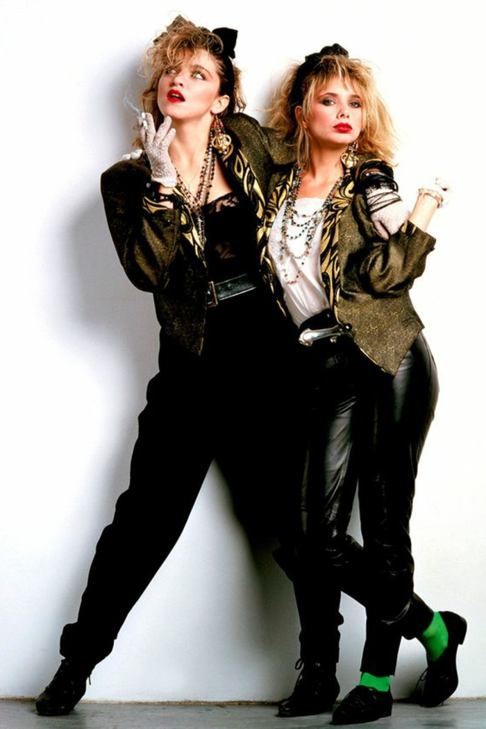 80s madonna with messy punk hair, red lipstick and black headband, in black outfit and shiny jacket with animal print details, holding cigarette with gloved hand and hugging a friend, wearing similar outfit