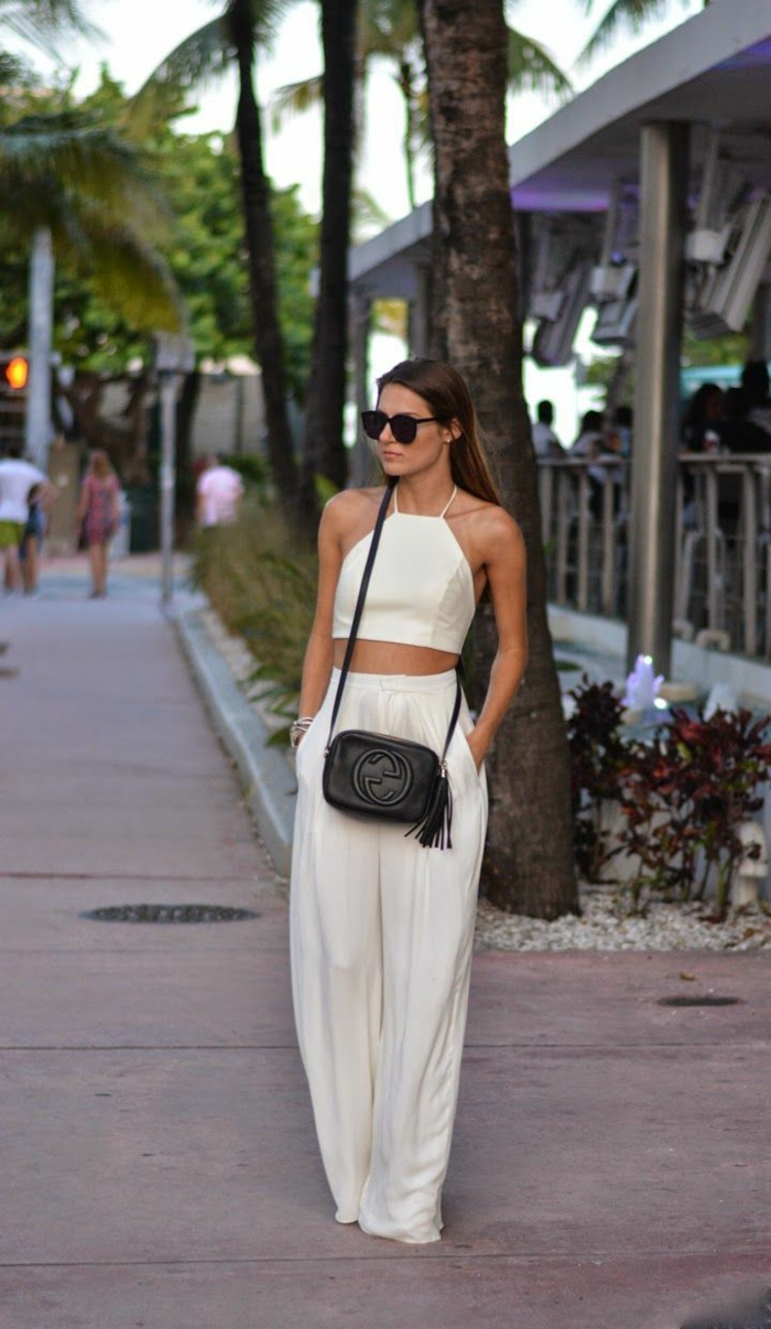 business casual for women, brunette wearing white, floaty baggy trousers, white crop top, sunglasses and a black designer cross-body bag