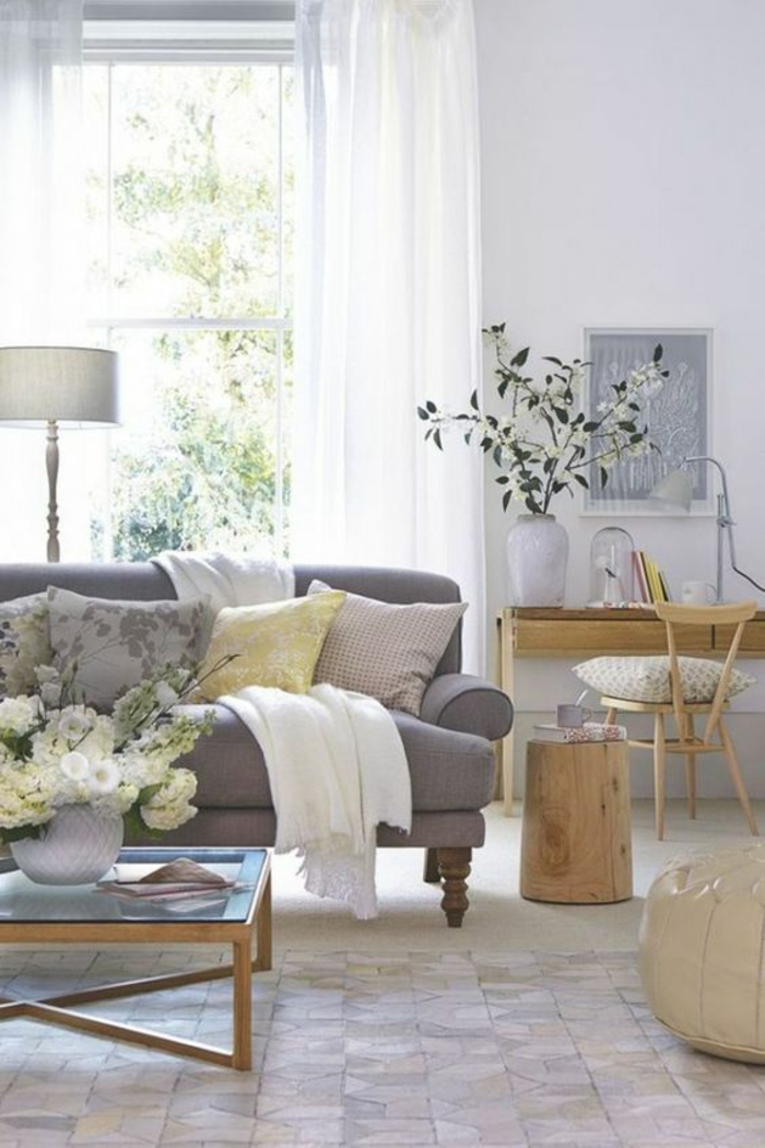 room with pale walls, grey sofa with four yellow and grey cushions and white blanket, wooden desk and chair, wooden coffee table with glass top, window with white curtains