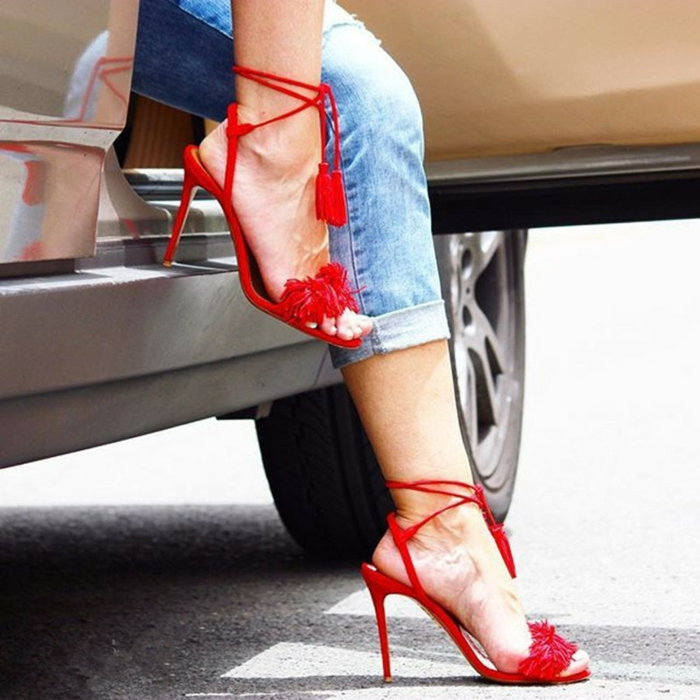 business casual for women, close up of woman's legs, wearing ankle jeans and strappy, red sandals with high heels and tassels