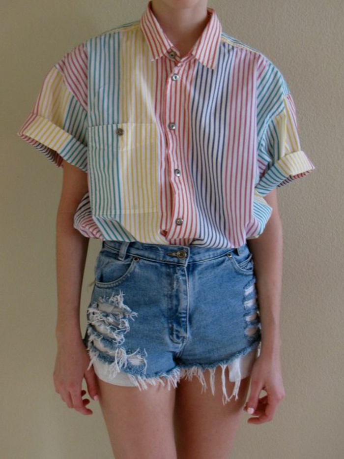 woman wearing over-sized shirt with cropped rolled sleeves and differently colored stripes, paired with ripped and distressed denim shorts