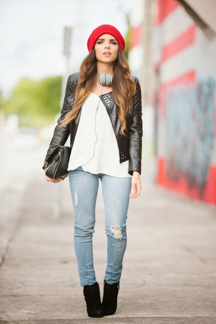 casual business attire, distressed jeans and white top, black biker leather jacket and black bag, worn by woman with long brown ombre hair, red beanie hat headphones and black shoes