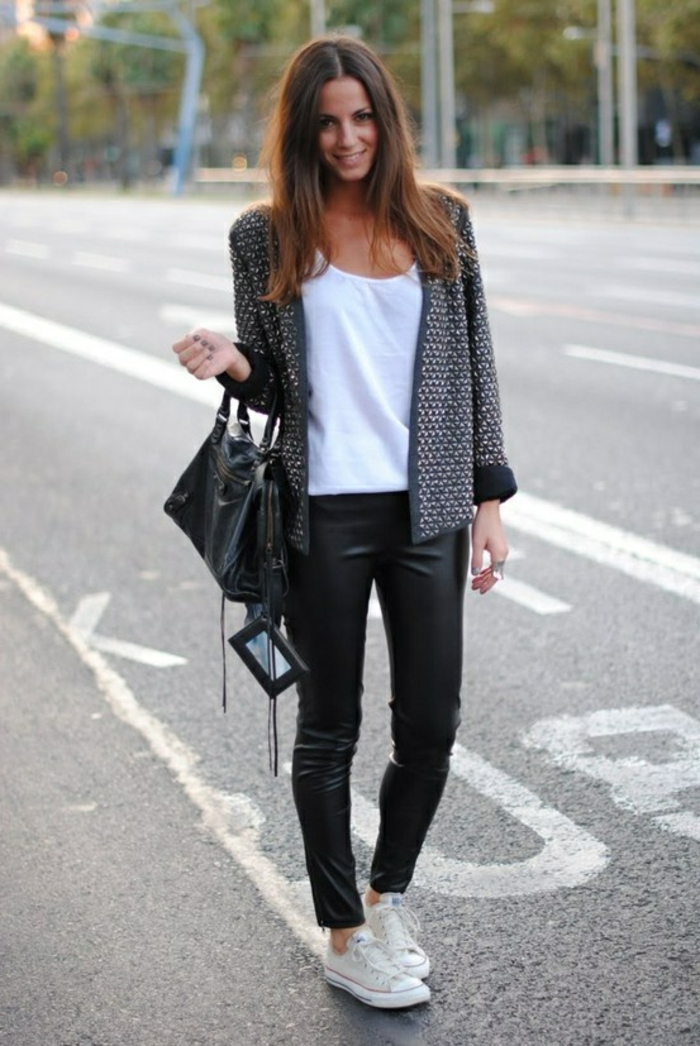 women's business attire, smiling brunette in black leather skinny trousers and white top, with dark grey cardigan, black leather bag and white sneakers