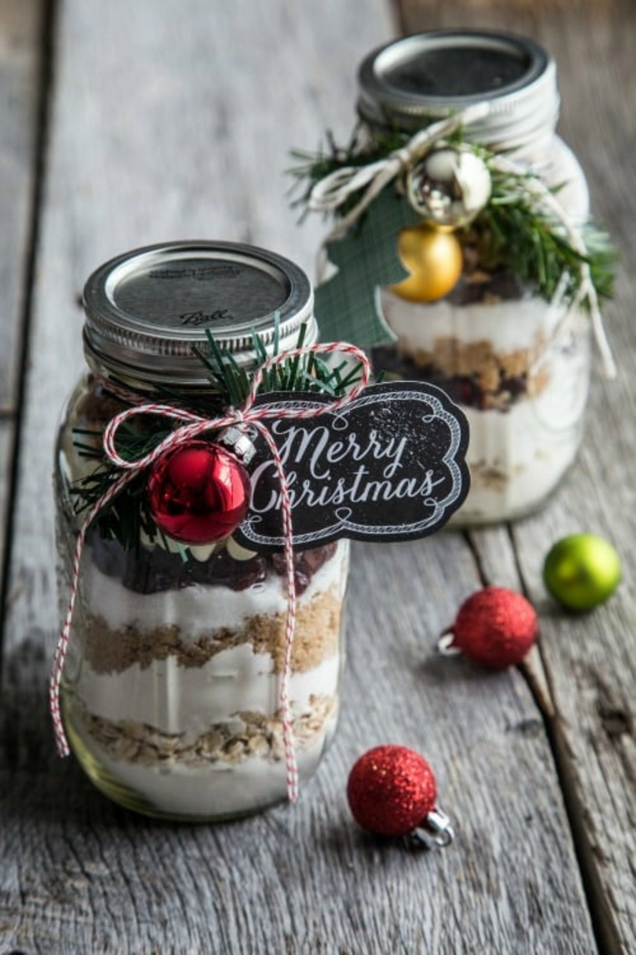 family christmas gifts, two jars containing layers of sugar flour and nuts, decorated with pine twig and xmas tree ornaments, black label tied with red and white string, red green yellow and silver ornaments