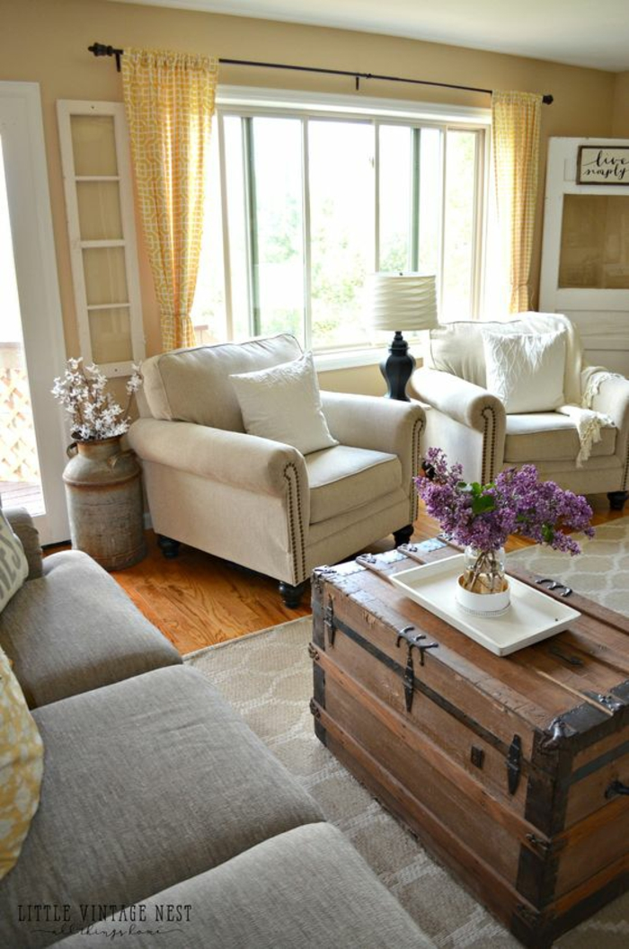 living room paint colors, pale yellow walls and curtains, light grey sofa and two cream colored chairs with pillows, big wooden chest used as table, white tray and a vase with lilacs