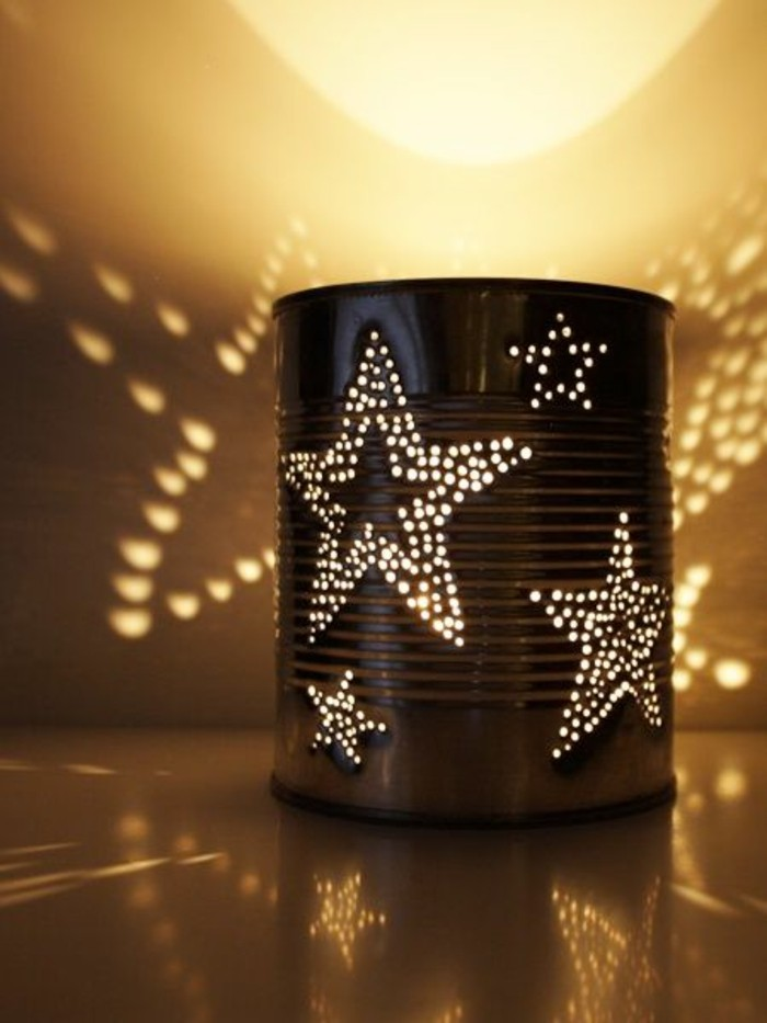 luminary made from tin can, with little holes forming star patterns, light from within projects star patterns on surface and wall