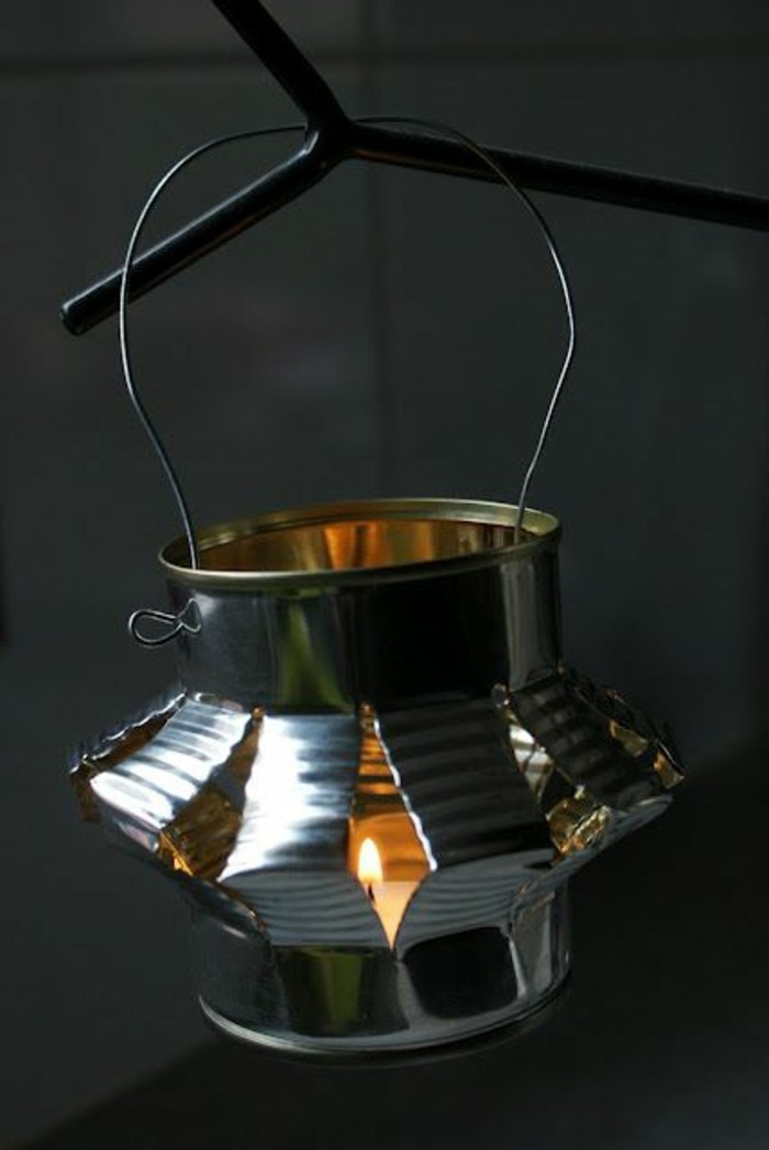 lantern made from cut and folded plain tin can, hanging from a wire handle, containing small lit candle