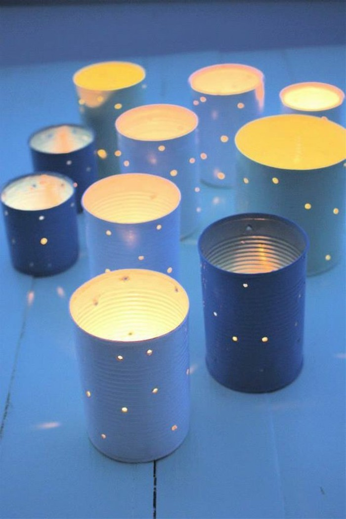 several luminaries made from cans in different sizes, painted in blue, with holes seeping light