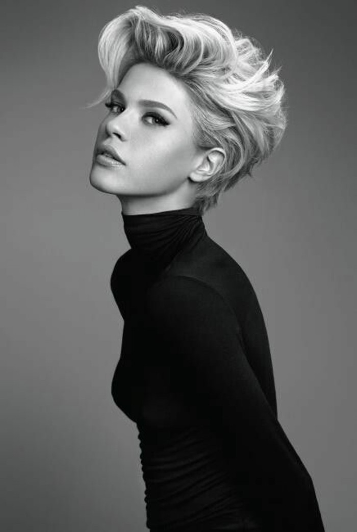 black and white photo of a woman, short gelled up blonde hair, black turtleneck and eyeliner