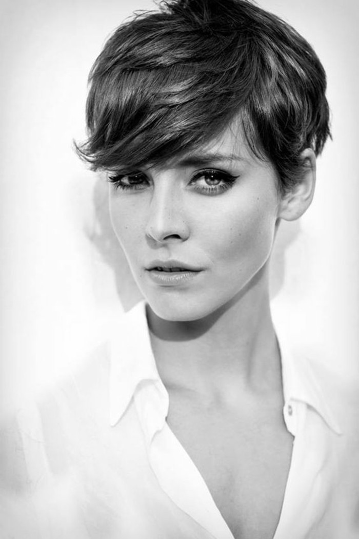pixie cut, black and white image of woman, with dark layered hair, side bangs above one eye, wearing white shirt and black eyeliner