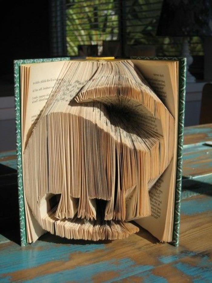 book folding art, a dinosaur shape, made from cut and folded pages, inside a vintage book, with green and white patterned hard covers
