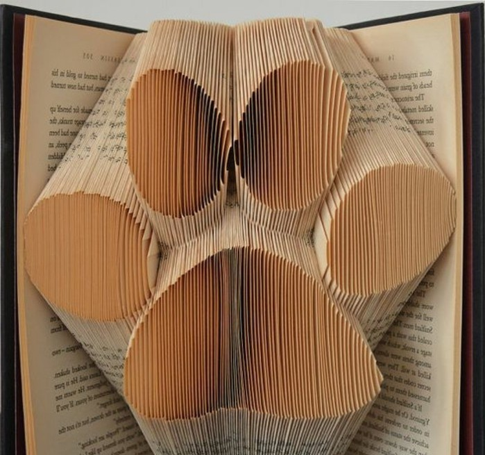 book folding art, giant paw print, made from folded pages, inside an open vintage book, with dark hard covers