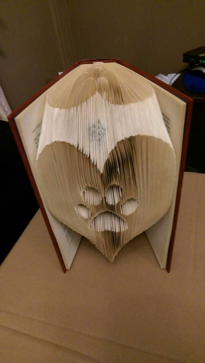 book folding art, heart shape with paw print, made from folded pages, inside an open book, with dark red hard covers