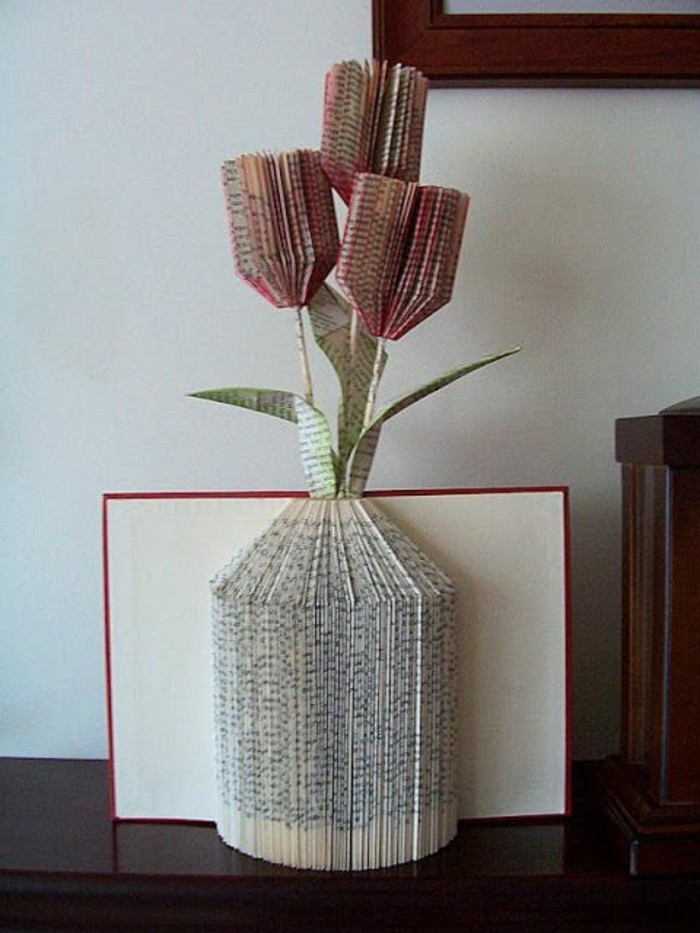 book folding art, book with red and white hard covers, opened to reveal a vase shape, made from folded pages, with paper flowers, made from more cut and folded pages, painted red and green