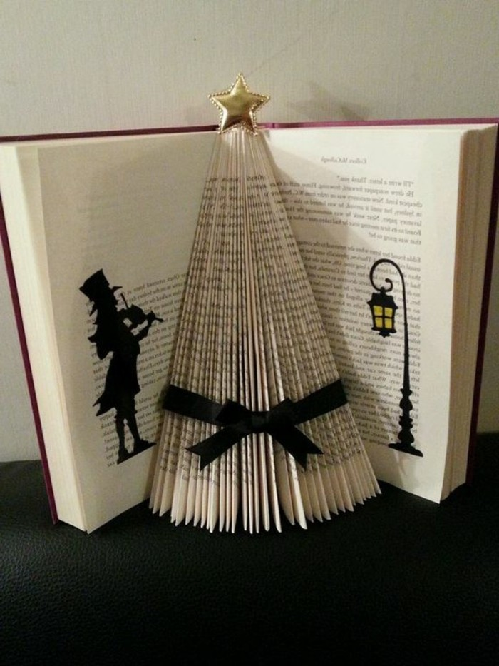book folding, open book with red covers, containing Christmas tree shape, made from folded pages, decorated with a black ribbon, and shiny gold star, black silhouette shapes, drawn in marker on nearby pages