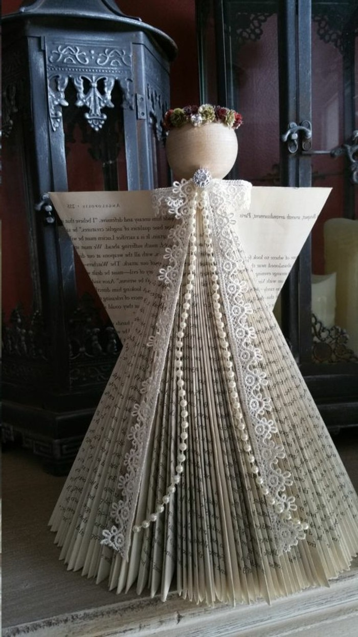 book folding patterns, angel shape made from cut and folded book pages, decorated with lace and pearl beads, with a round wooden head, and a faux flower crown