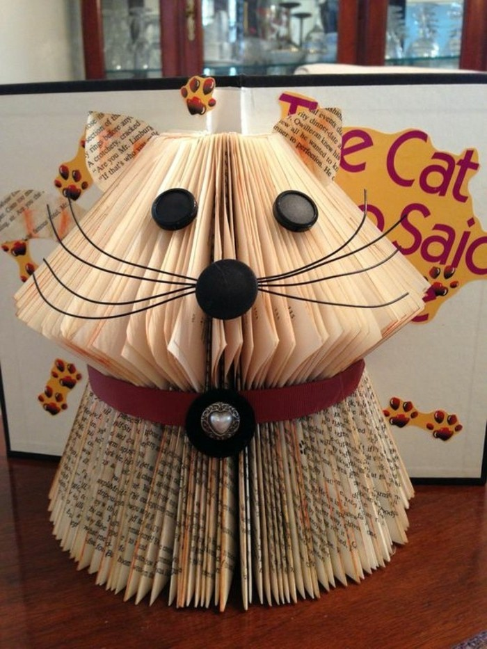 book folding patterns, small cat ornament, made from cut and folded book pages, decorated with round black plastic buttons, wire whiskers and a red collar