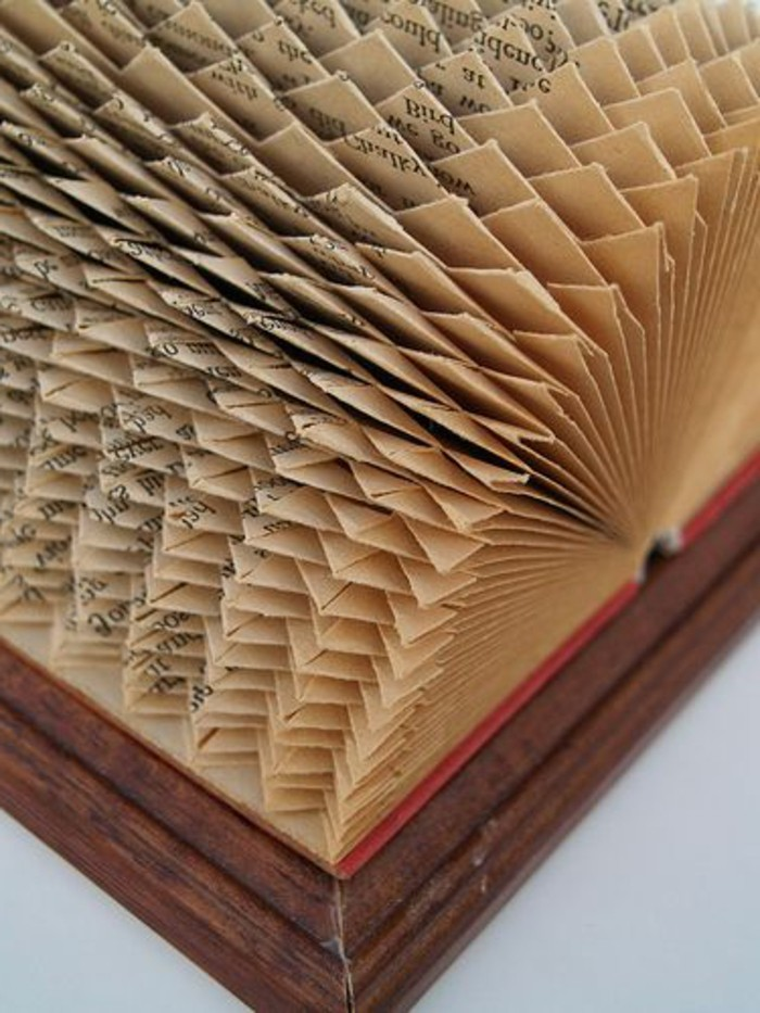 book folding patterns, vintage book with red covers, placed in wooden frame, opened to reveal intricate geometrical pattern, made from folded pages