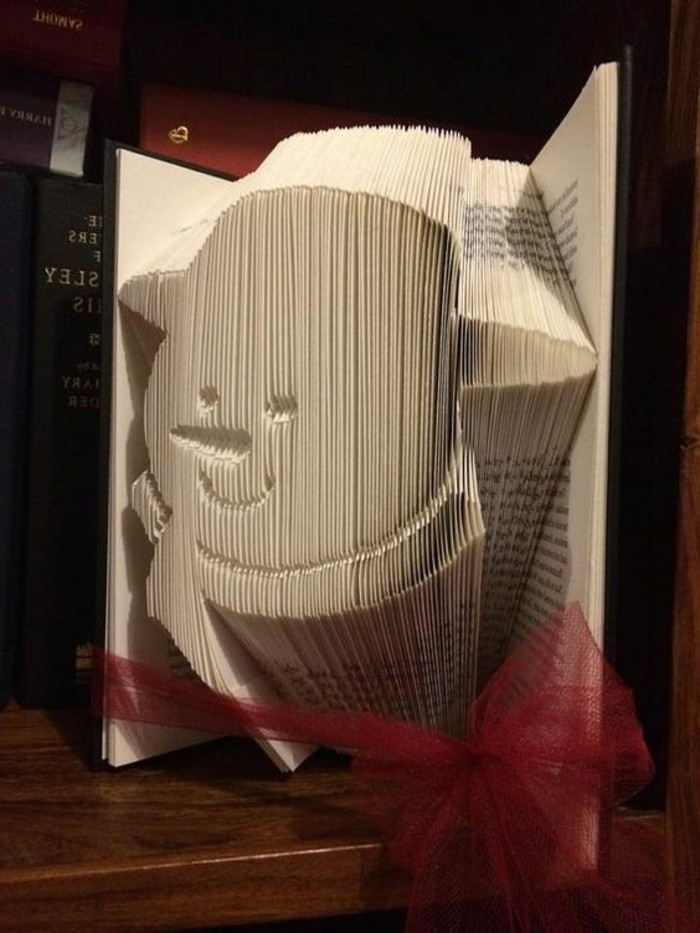 book folding patterns, opened book with black covers, tied with a sheer red ribbon, showing a smiling snowman's head, made from folded pages