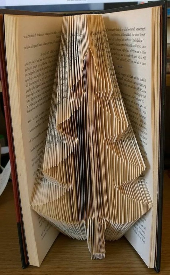 christmas tree shape made from folded pages, inside an open vintage book, with yellowy pages, and brown hard covers