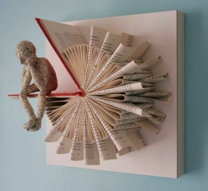 bookfolding, art piece made from an opened book, with hard red covers and folded pages, glued to a canvas, and made to look like a watch, human figure made from white cracked stone, sitting on one cover