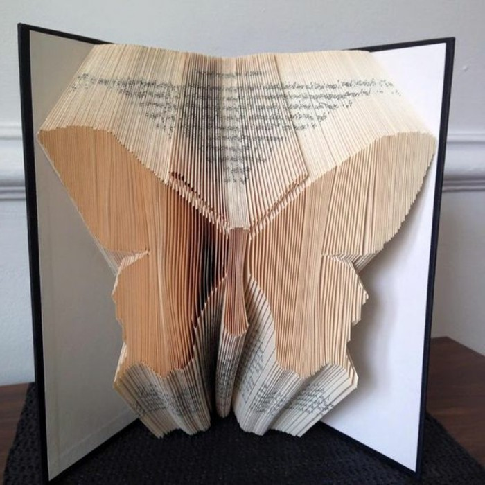 book folding, symmetrical butterfly shape, made from folded pages, inside an open book, with black and white hard covers