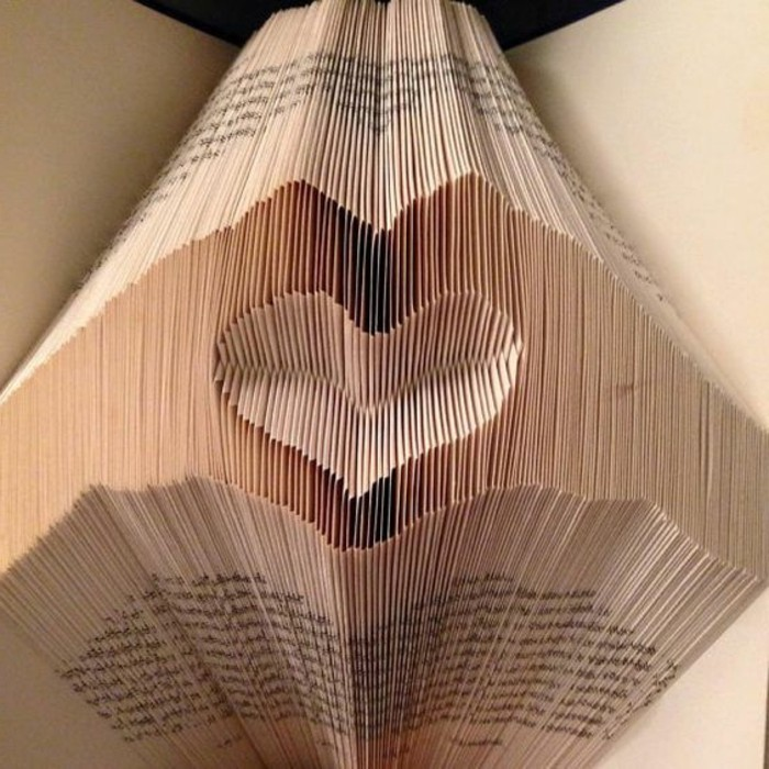 open book with vintage-looking pages, folded to create two hands, making a heart shape