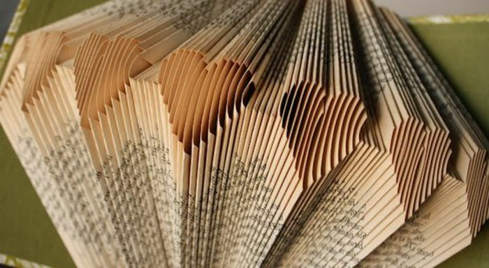close up of vintage book pages, folded to create heart shapes, green and white covers of a book, are visible in the background