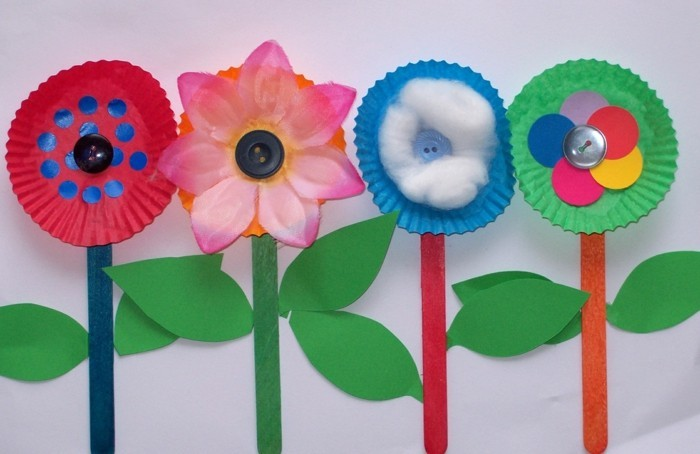 diy projects for kids, four flowers made from cupcake moulds in different colors, attached to ice cream sticks, decorated with green paper leaves, buttons and cotton