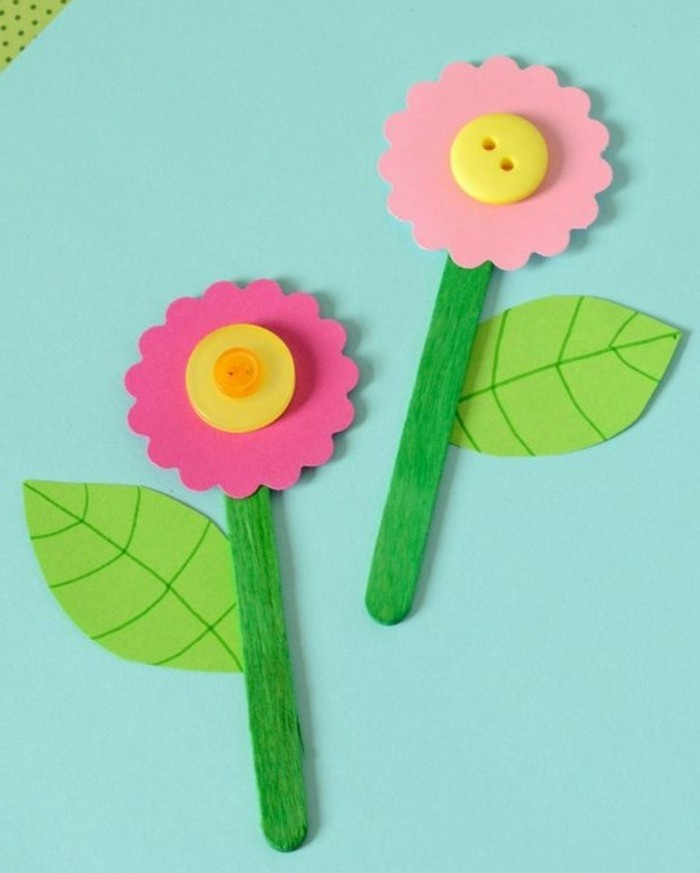 craft ideas for kids, two flowers made from pink felt, yellow buttons and green paper leaves, attached to ice cream sticks painted in green