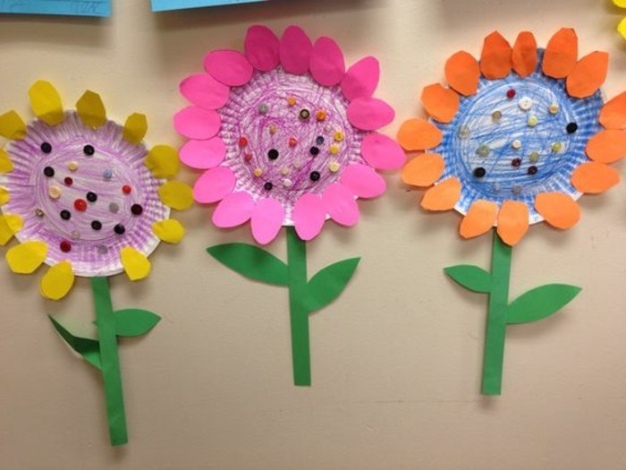 craft ideas for kids, three flowers made from paper plates, colored with pencils, with stalks made from green paper and petals made from yellow, pink and orange paper