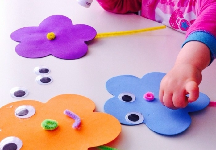 diy art projects, toddler's hand sticking paper to a flower-shaped cutout, finished purple and orange flower cutouts nearby
