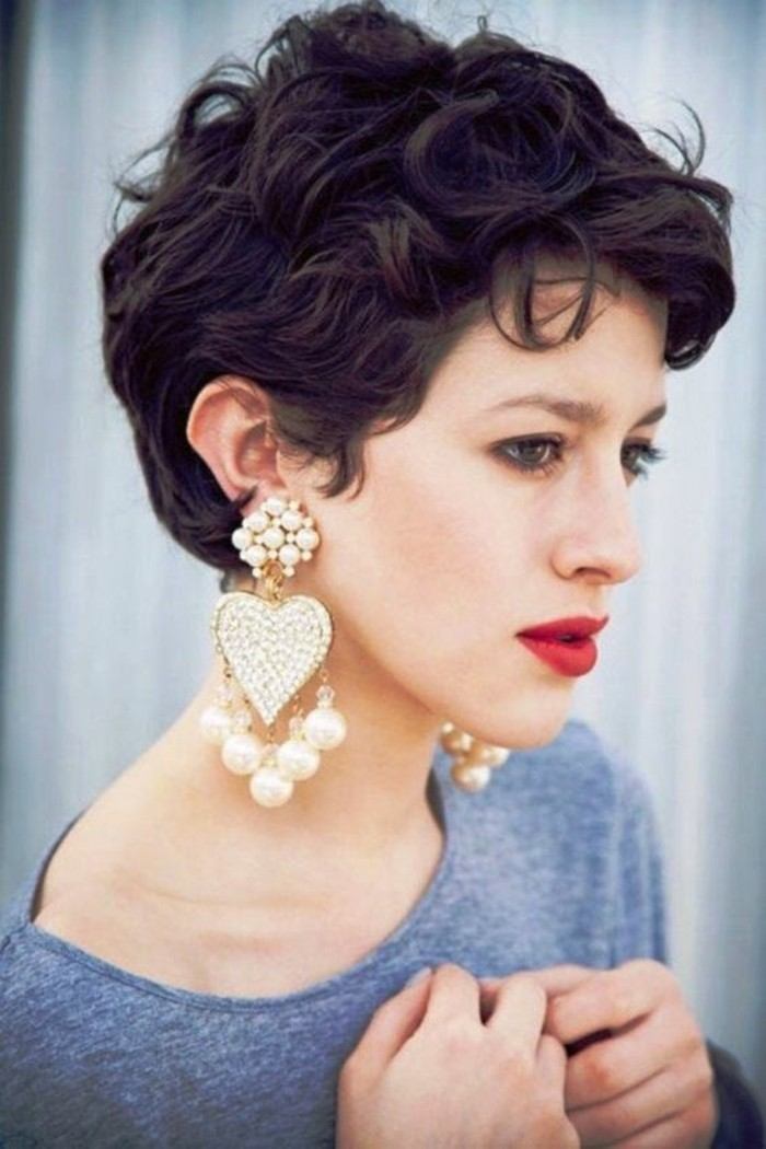 haircuts for women, close up of a woman with very short, dark brown curly hair, grey top and big, heart-shaped earrings with pearls