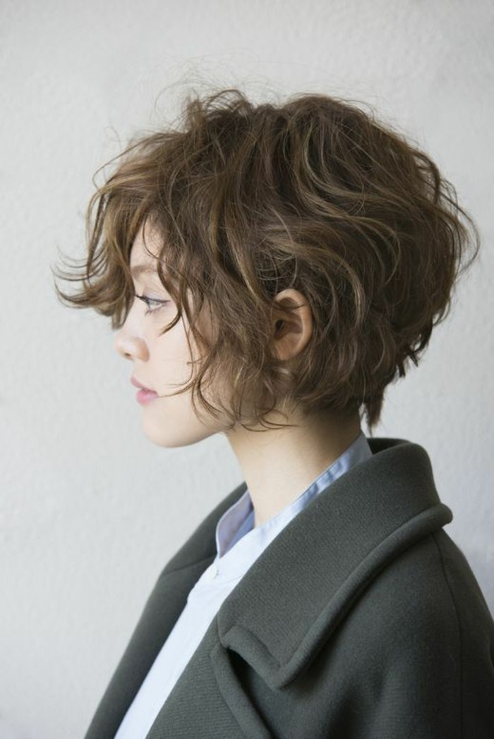 cute hairstyles, young woman facing to one side, with messy curly brown hair, wearing black woolen coat and blue shirt