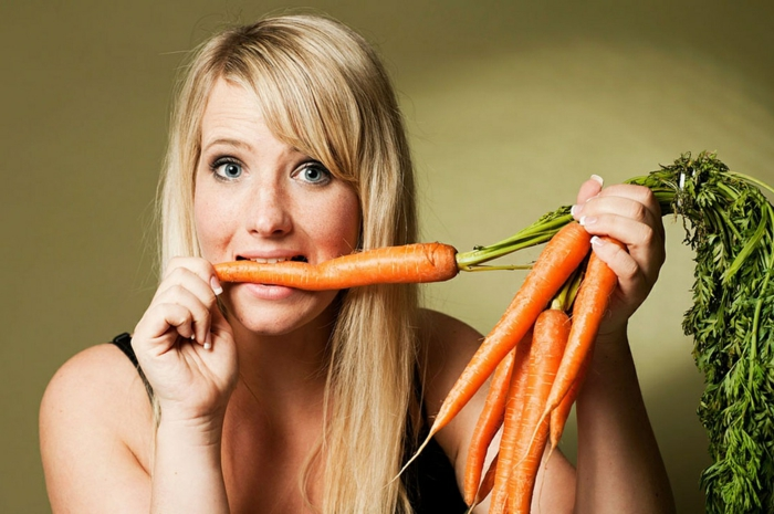 dark blue eyes, blonde woman with long hair and side bangs, holding a bunch of carrots in one hand, and biting onto one
