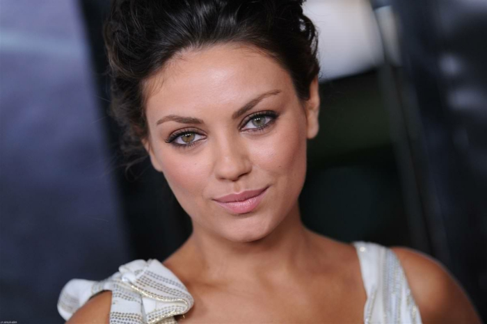 different colored eyes, mila kunis with dark hair tied up and white top, one of her eyes is hazel, while the other is blue