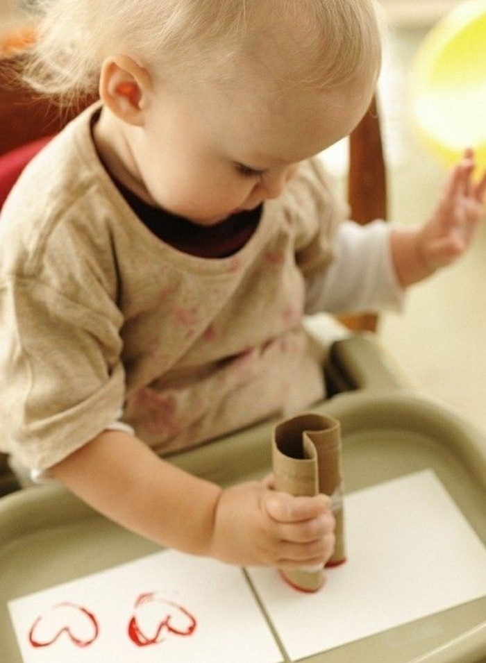 blond toddler in grey shirt, using a paper roll to stamp red heart-shapes on two white pieces of paper, placed on a plastic tray