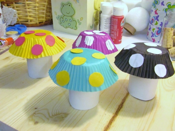 cool things to make at home, four mushrooms made from white paper, and muffin moulds in different colors, decorated with pink white and yellow paper dots