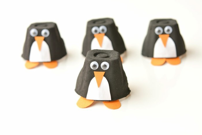 diys for your room, four penguin decorations, made from black cardboard cups, decorated with white and orange textured paper details, and stick on eyes