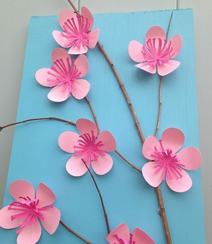 diy projects for kids, small twig decorated with cherry blossoms, made from paper in two shades of pink, on a pale blue background