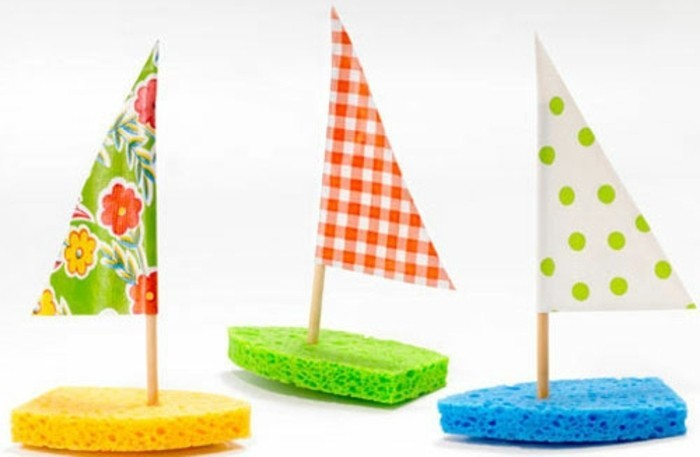 fun art projects, three boats made from sponges in yellow, green and blue, decorated with triangular sails made from colorful crepe paper
