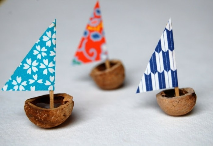 easy kids crafts, three little boats made from walnut shells, decorated with colorful triangular crepe paper sails on toothpicks