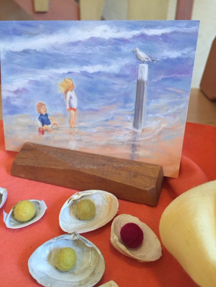 summer crafts for adults, several seashells containing small, round fabric decorations in yellow and red, near a painting of two children, looking at a seagull