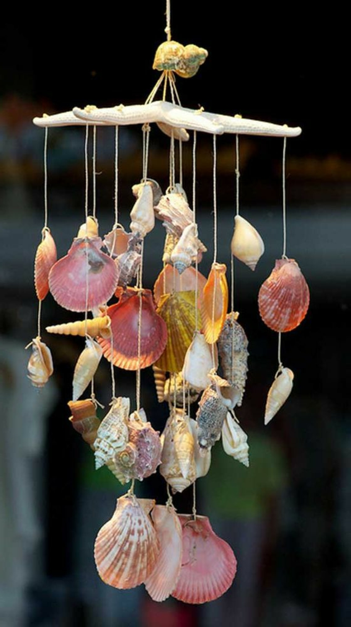 diys to do with friends, many differently shaped, colored and sized seashells, tied to a large dry starfish, to form a wind chime