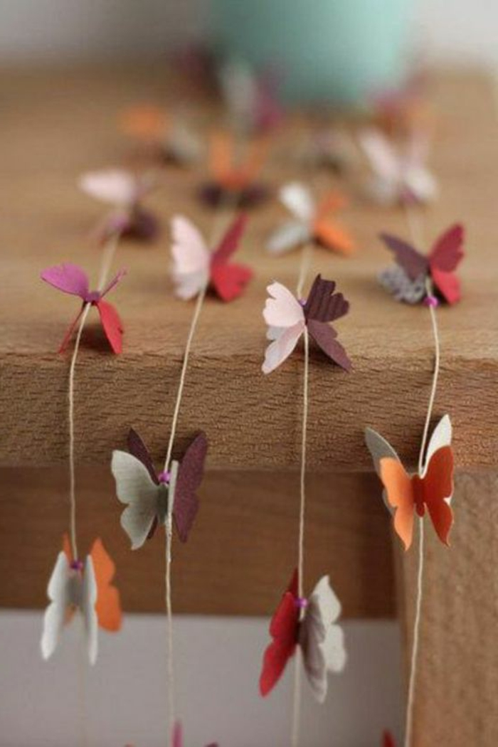diys to do with friends, four garlands made from burlap thread, decorated with felt butterfly shapes in orange, grey and purple, pink and red