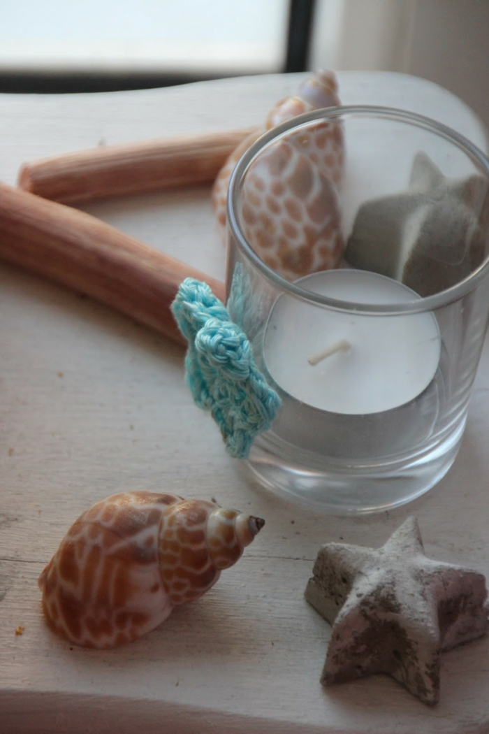 diys to do with friends, small glass decorated with teal knitted star, containing one tiny candle, seashells and starfish nearby
