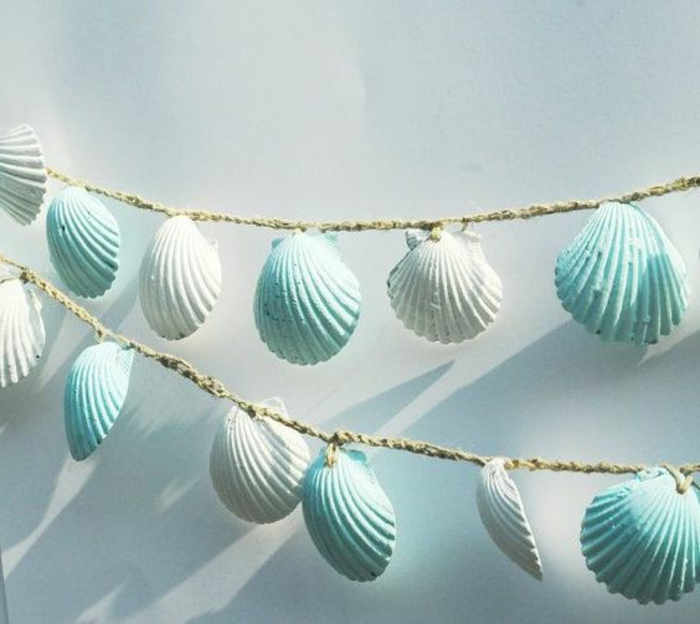 diys to do with friends, two garlands made from woven burlap thread, decorated with many seashells, painted in white and pale blue