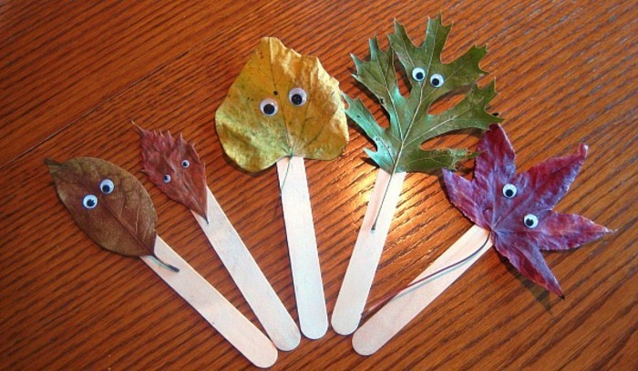 cool things to make at home, five autumn leaves in different shapes and colors, decorated with stick-on eyes, stuck on ice cream sticks