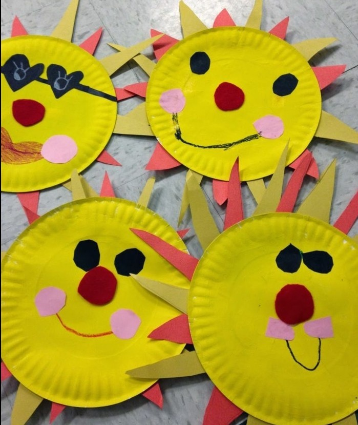 four suns made from yellow paper plates, decorated with black and red, and pink and yellow felt cutouts